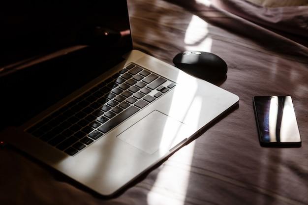 女性の服、スマートフォン、ラップトップ、ベッドの上にレイアウト、光