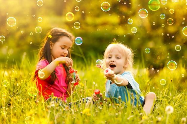 屋外で彼女の祖母とシャボン玉を吹く少女
