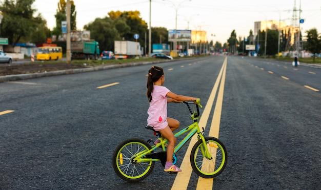 外の私道で自転車を運転することを学んでいる子供たち。ヘルメットを身に着けている都市のアスファルト道路で自転車に乗る少女たち。