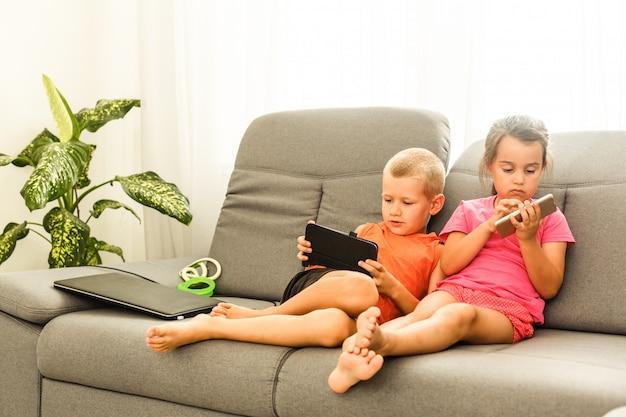 兄と妹が携帯電話を使用して自宅でソファに座っています。デバイスの画面を見て驚いた娘とイライラした息子を閉じます。ガジェットにはまっている新世代のテクノロジー