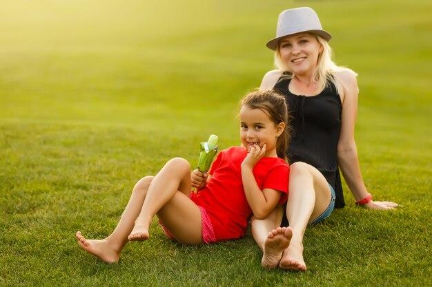 座っている草をリラックスした美しい若い母娘