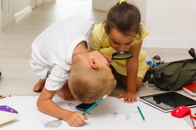 Детский мальчик и девочка рисуют, играя с увеличительным стеклом