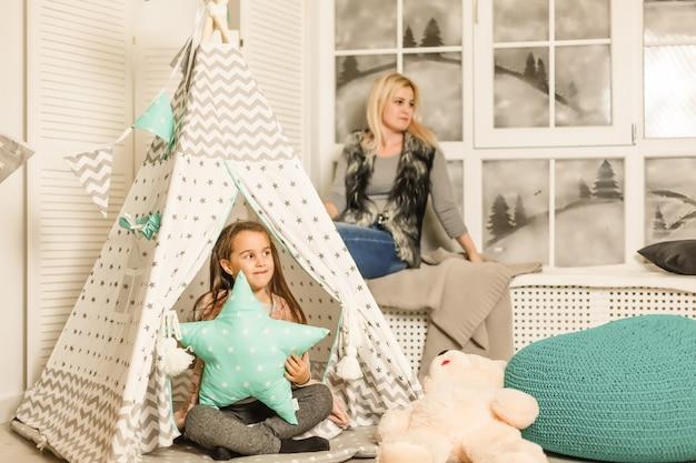 Молодая мама в сером свитере и дочка сидят в детской комнате зимой.