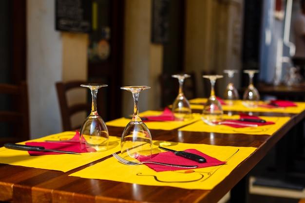 黄色とピンクのナプキンを持つ木製のテーブルの上の空の反転メガネ