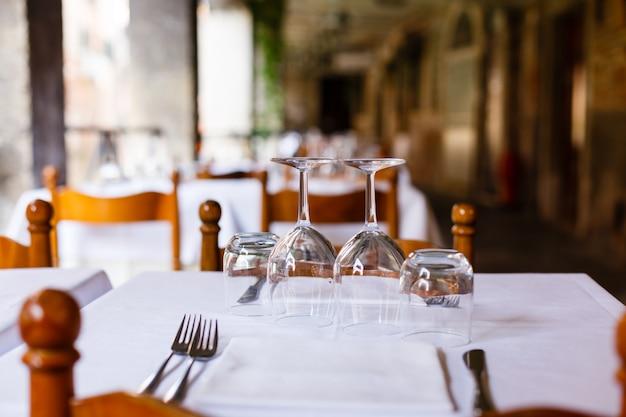 レストランで白いテーブルクロスをかけた木製のテーブルの上の空の反転メガネ