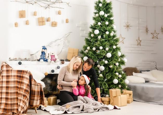 新年。クリスマス。家族。若い親とサンタ帽子の小さな娘は、自宅のクリスマスツリーの近くで一緒に時間を過ごしています
