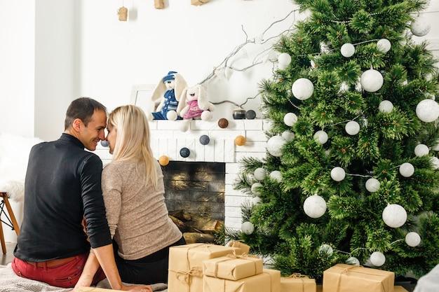 暖炉の前でカーペットの上に座って素敵な愛のカップル。女と男のクリスマスを祝う