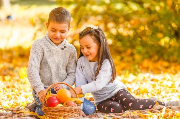 Счастливые дети едят красное яблоко во время прогулки в осеннем парке
