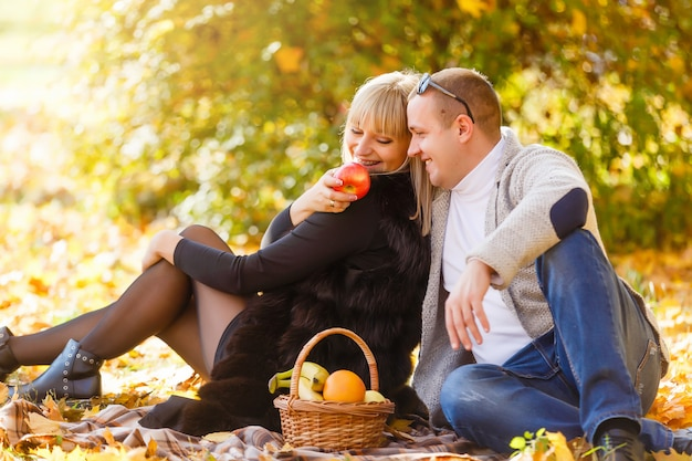 秋の落ち葉の上に座って、美しい秋の日を楽しんでいる愛のカップル。おでこに女性にキスをする男性