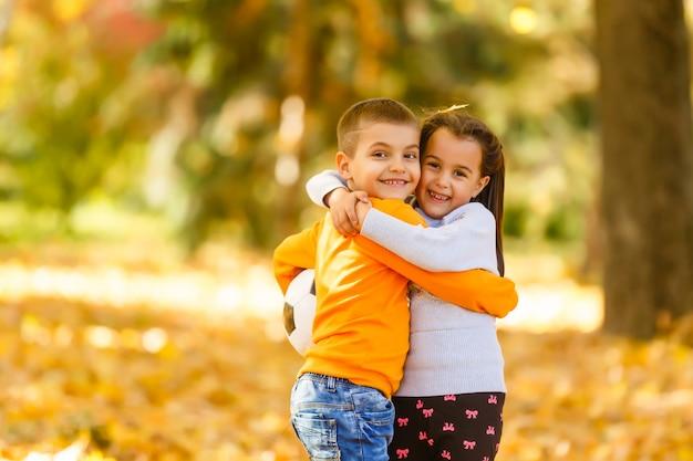 公園で秋の落ち葉で遊んでいる子供たち