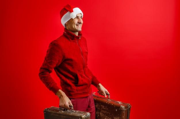 クリスマス、観光旅行のコンセプト。スーツケースを持ったサンタクロースは地球を旅します。クリスマスの時期。
