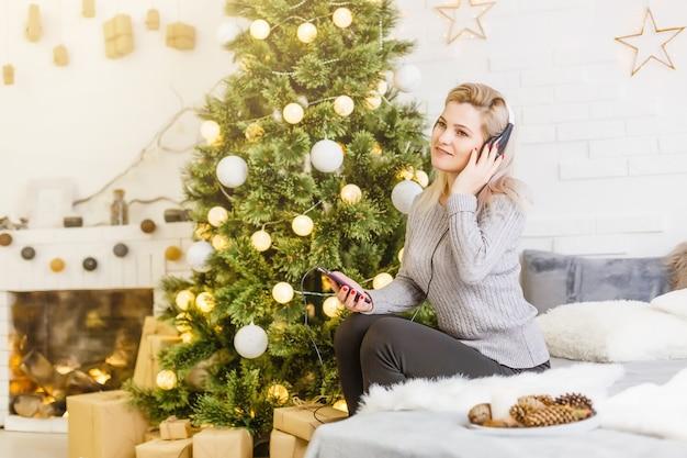 クリスマスに彼女の音楽を楽しむ幸せな女