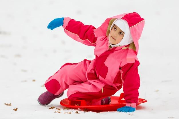ジャケットと雪に覆われた冬の公園で遊んでいるニット帽子を着て美しい少女