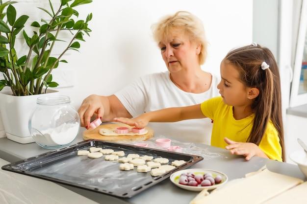 Маленькая девочка делает печенье из теста на кухне дома