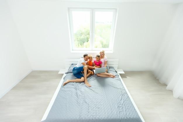 自宅の寝室でラップトップを使用してベッドの上の幸せな家族