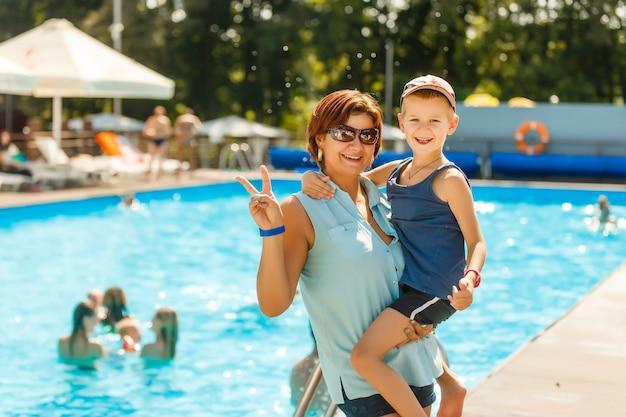 スイミングプールに立っていると暖かい夏の日に休暇中に笑っている彼女の息子を持つ美しい母親のクローズアップの肖像画