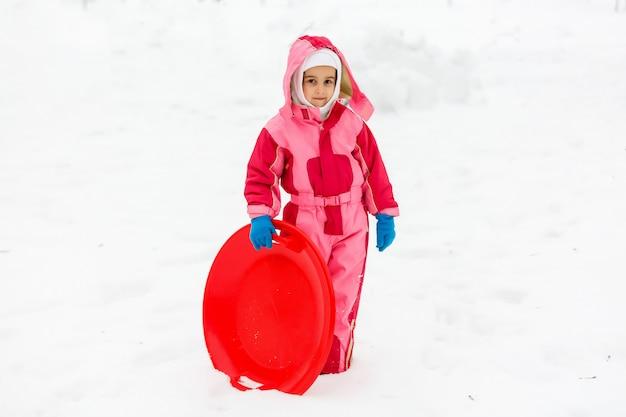 雪の上に乗って小さな女の子が冬時間でスライドします。