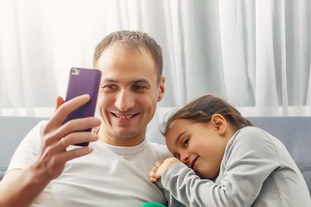ソファのスマートフォンに座っている夕方の父と娘の中で。