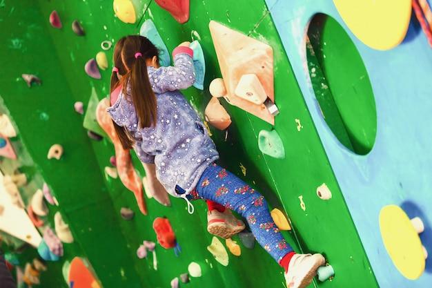 屋内の実用的な壁に登っている女の子