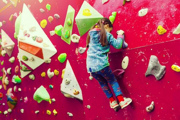 アトラクションの遊び場で壁に登る少女