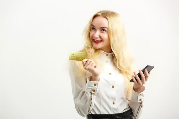 カメラを見ながらクレジットカードと携帯電話を保持している笑顔の幸せな女