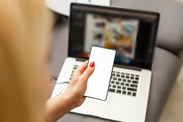 カフェでノートパソコンとスマートフォンを使用して女性