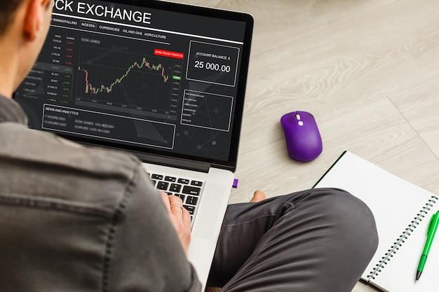 Бизнесмен сидит и с помощью ноутбука, показывая график торговли