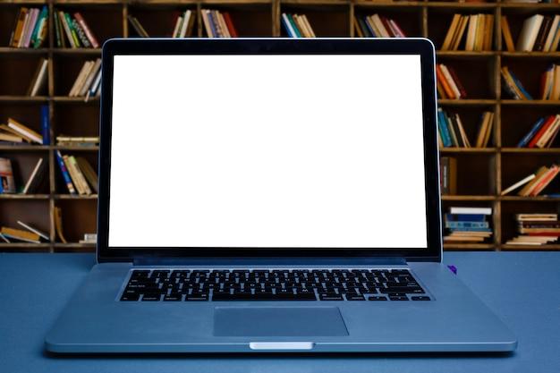 本棚の背景に木製のテーブルの上の携帯電話で空白のノートパソコンの画面