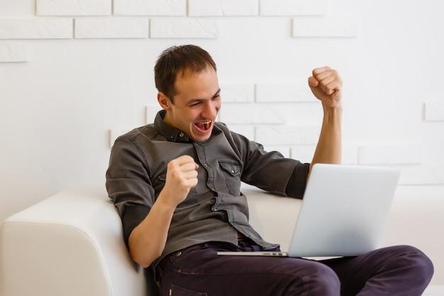 Счастливый азиатский человек используя компьтер-книжку в живущей комнате.