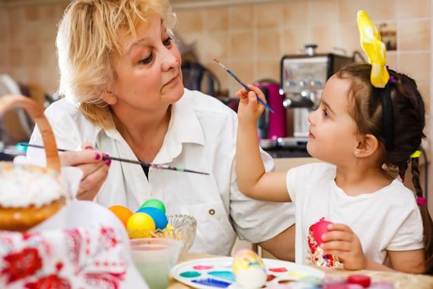 孫娘と祖母はイースターの卵を着色しています。
