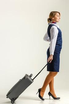スチュワーデスが行き、スーツケースを転がします。