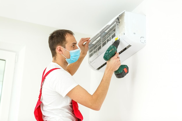 室内のエアコンを掃除する男性技術者
