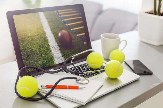 ノートパソコン、スポーツ用品、テニスボール、スポーツ管理の白いテーブルの平面図。