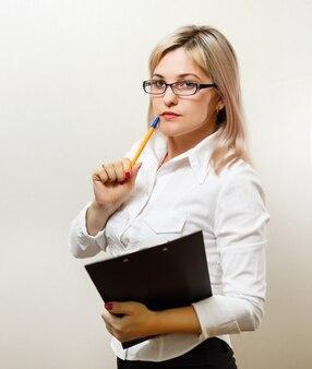 クリップボードに書いて幸せな笑みを浮かべて陽気な若い実業家