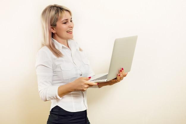 立っているとラップトップを保持している笑顔の素敵な若い実業家