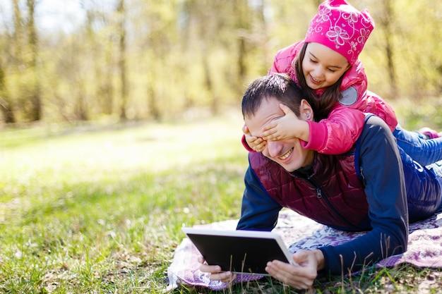 Отец показывает игру в планшетный пк своей дочери в парке