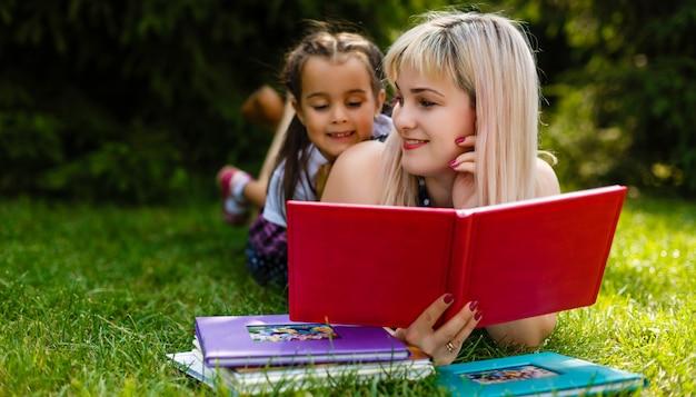 緑の牧草地で彼女の小さな娘に本を読んでかなり若い母親