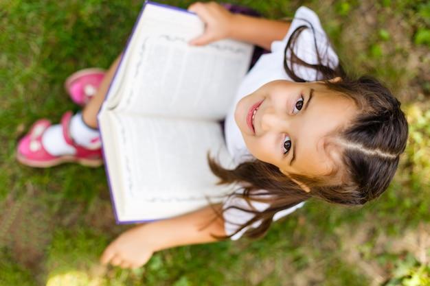 Портрет маленькой милой книги чтения девушки, сидя на парке зеленого цвета лета.