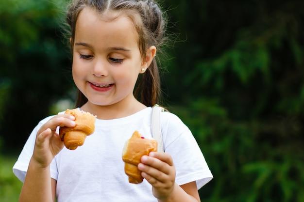 Молодая девушка ест круассан