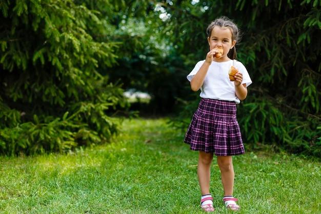 Маленькая школьница ест круассаны в парке. снова в школу на улице