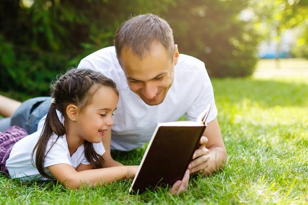 小さな娘を持つ若い父親が聖書を読む