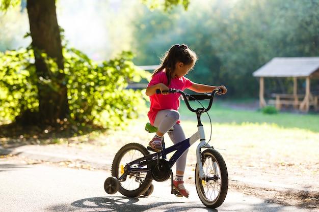 青い髪の少女は、日没で自転車に乗る。日没時の子供乗馬自転車