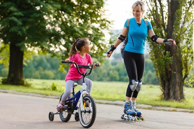 Мать катается на роликах. дочь катается на велосипеде