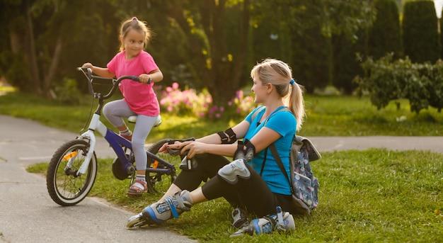 ローラーを置く公園に座っている女性。自転車に乗る娘