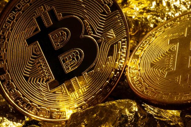 Крупным планом большой золотой самородок и золотые биткойны монеты на черном фоне криптовалюты биткойны
