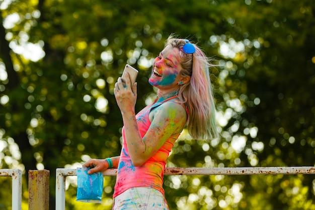 携帯電話を使用してホーリーカラーフェスティバルで幸せな若い女の子
