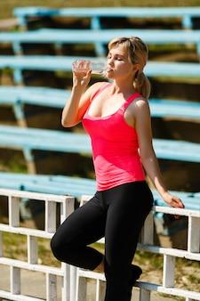 ハードトレーニングの後、新鮮な水と残りの部分を飲むフィットネス女性アスリート
