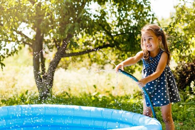 小さなプールに水を注ぐ少女