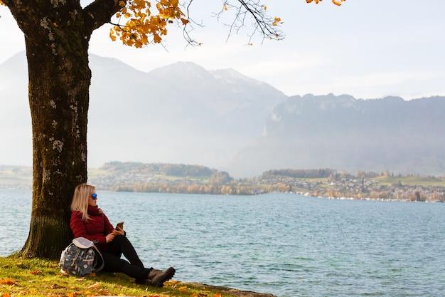秋の湖の近くに座っている秋の居心地の良い、美しい女性