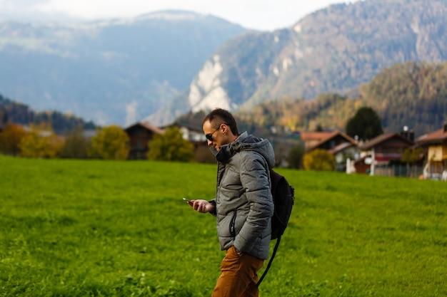 スイスアルプスの田舎道を歩いてガジェットを持つ男ツーリスト